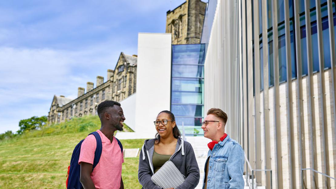 Students outside pontio with the University's Main Arts Building in the background