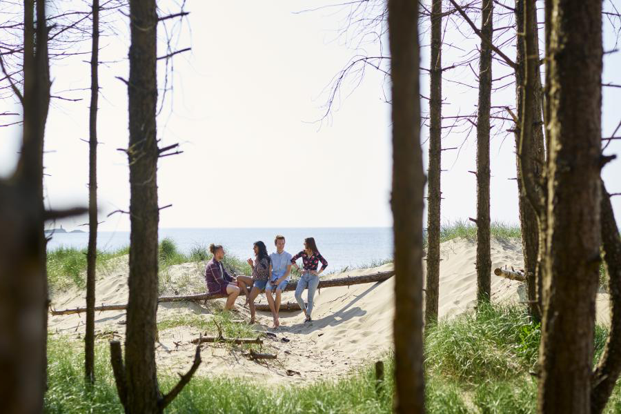Students sitting on the beach in nearby Llanddwyn