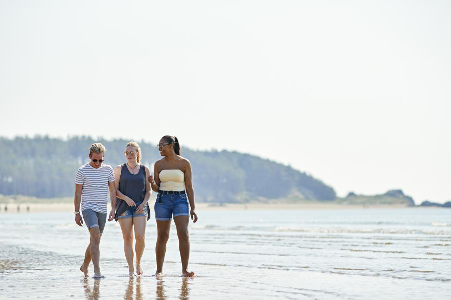 Three students walking along the beach