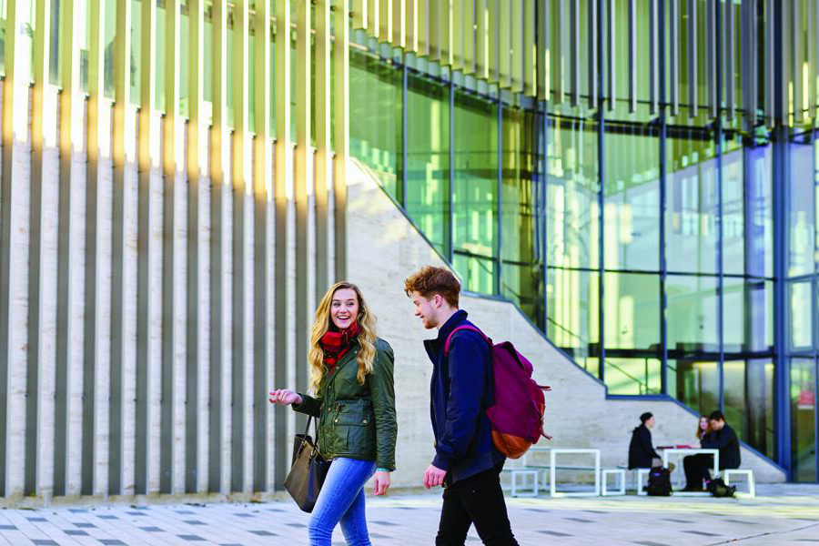 Two students chatting walking outside the pontio building