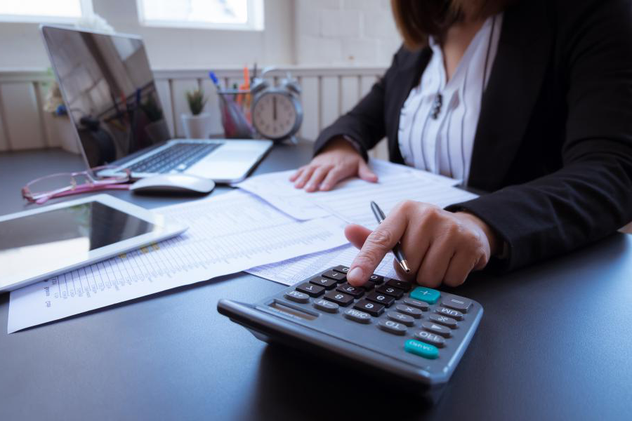 professional working on finances at a desk with a calculator and laptop